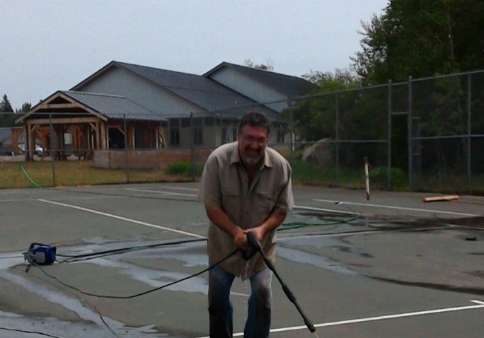 Marc Smith pressure washing the cracks on the tennis court in preparation for patching.